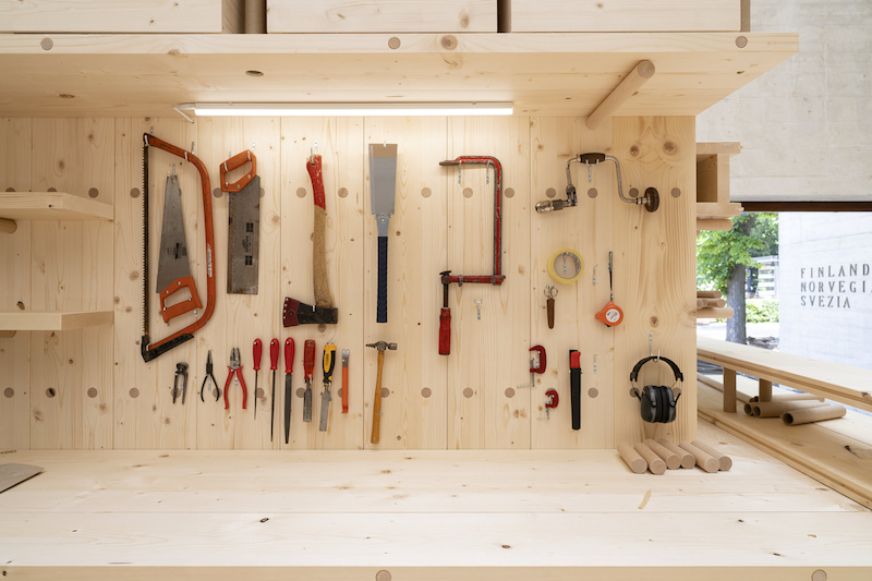 a detail view of some tools on a wooden hanging board