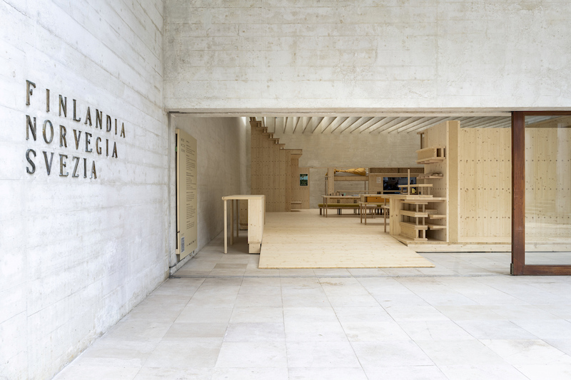 a view from the outside of the nordic pavilion in venice, a concrete building with large open windows, inside is a wood construction