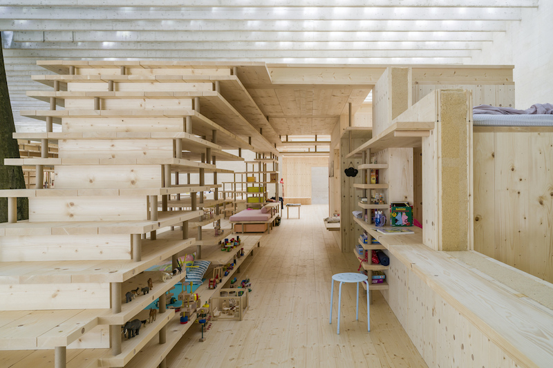 a view of the wooden construction inside with a stool and kids toys on the shelves