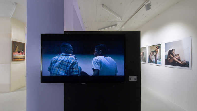 a screen with two people their backs facing the viewer hangs in the middle of an exhibition space, with photos and paintings on the walls behind it