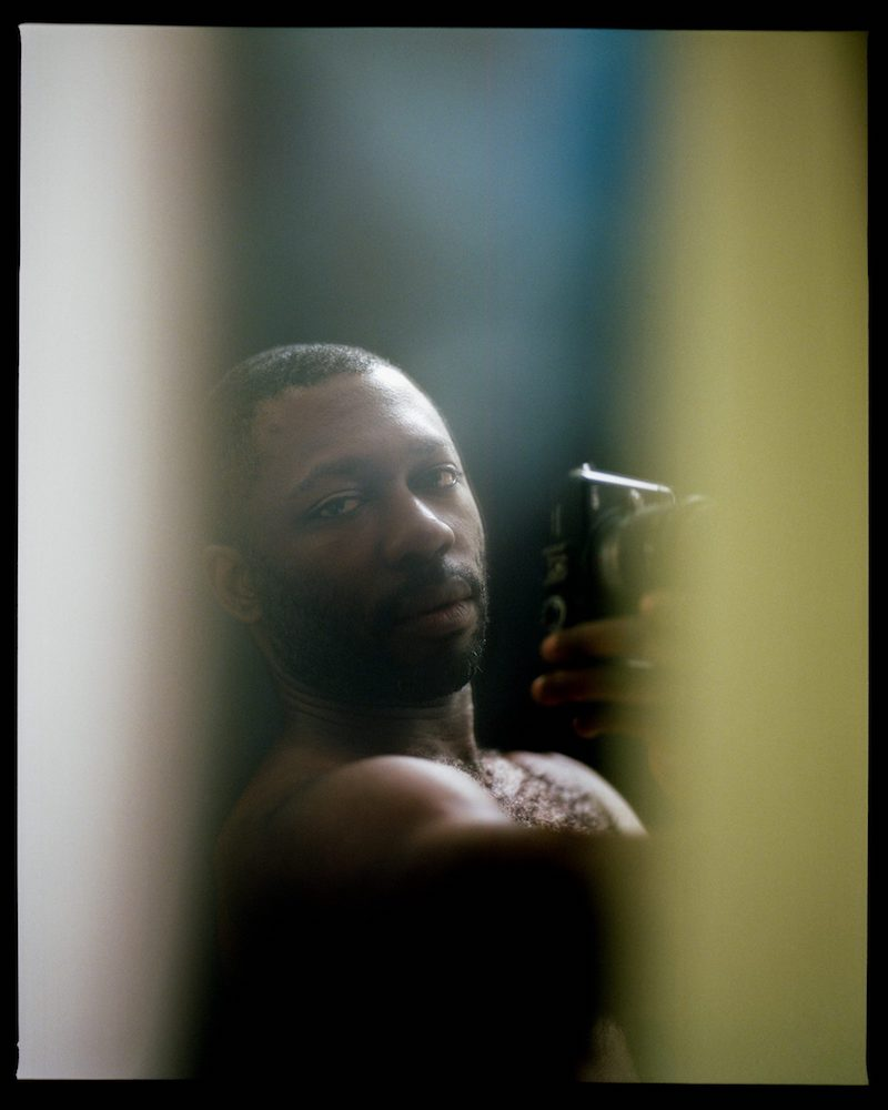 a black man looks into a mirrored surface, taking a photo of himself with an analog camera