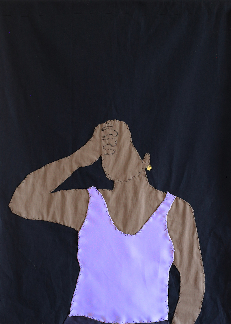 a textile work on black fabric with a brown skinned woman holding her hand to her forehead