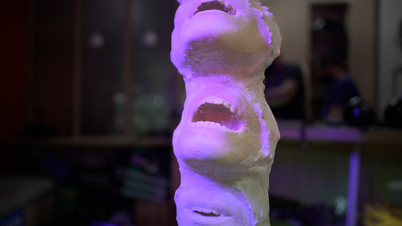 a close up shot of a tower sculpture made up of open mouths, and bathed in purple light