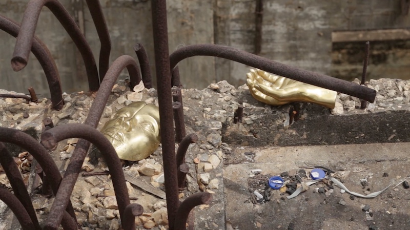 a construction site with metal sticking out of concrete and two gilded body parts lying on top, a hand and a face