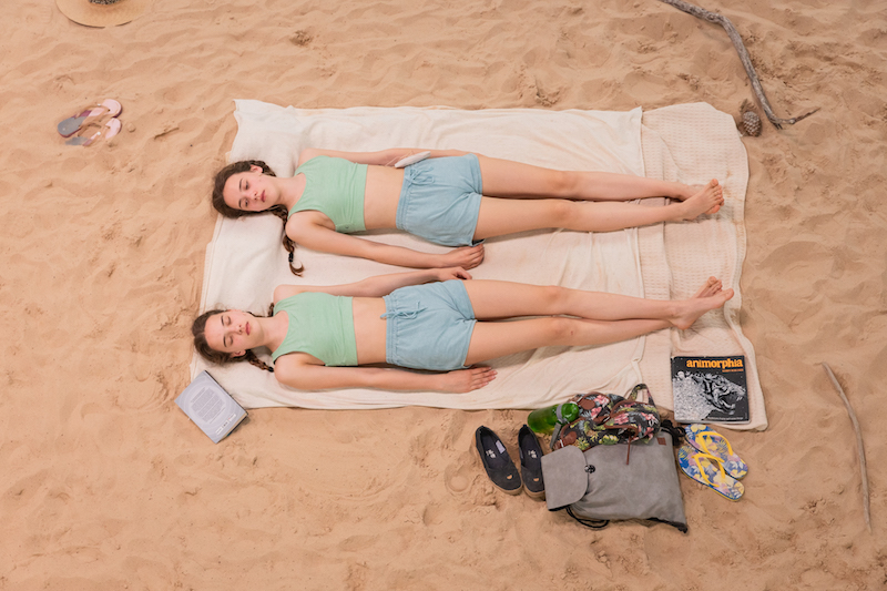 twin girls wearing matching blue shorts, sage green crop tops and long braids lie on a beach towel on the sand