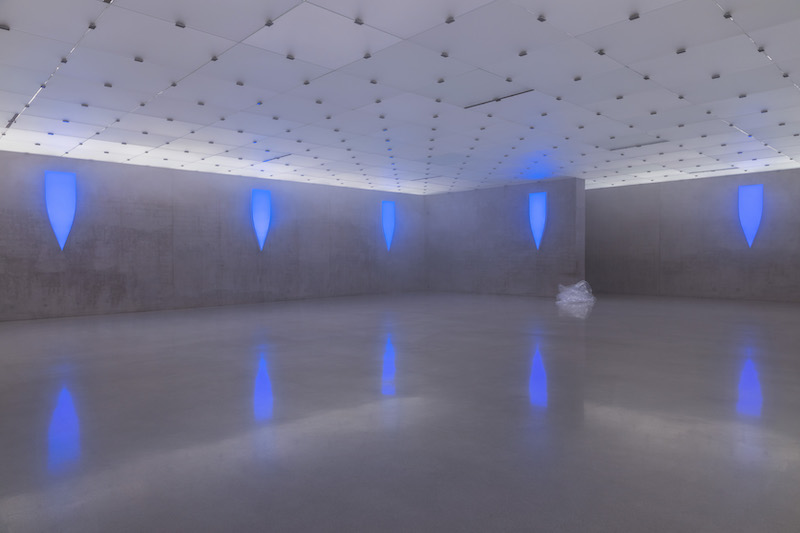 An exhibition space at Kunsthaus Bregens showing blue lights on the concrete walls
