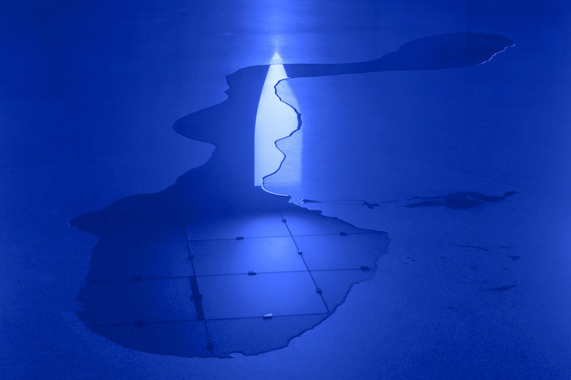 A blue lighted exhibition space at Kunsthaus Bregens showing a blue light reflected onto the wet floor