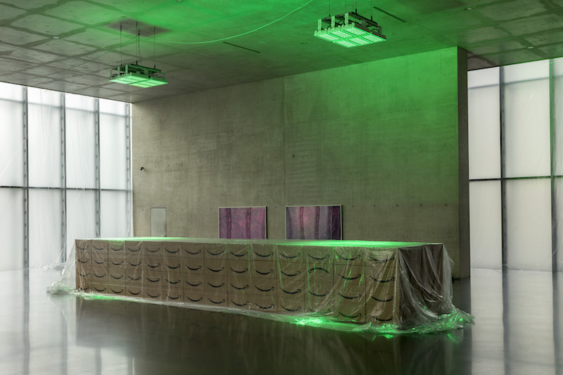Desk constructed of Amazon shipping boxes covered with plastic foil in the green LED lighted exhibition space at the first floor of Kunsthaus Bregenz