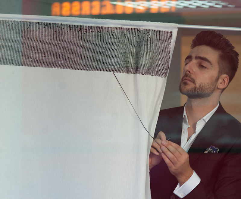 the artist stands behind a hanging piece of white fabric, embroidering black thread onto it from the side