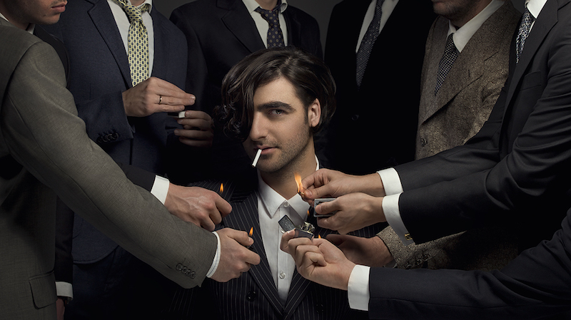 the artist sits in the middle of the photo's frame, staring into the camera, while several men's hands in suits reach out to light a cigarette in his mouth