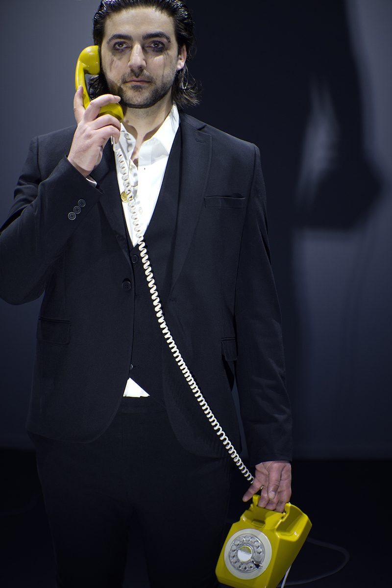 the artist stands in a room, visible from the window outside on the street, wearing a black suit and white shirt, with mascara running down his face and a yellow rotary telephone in his hand