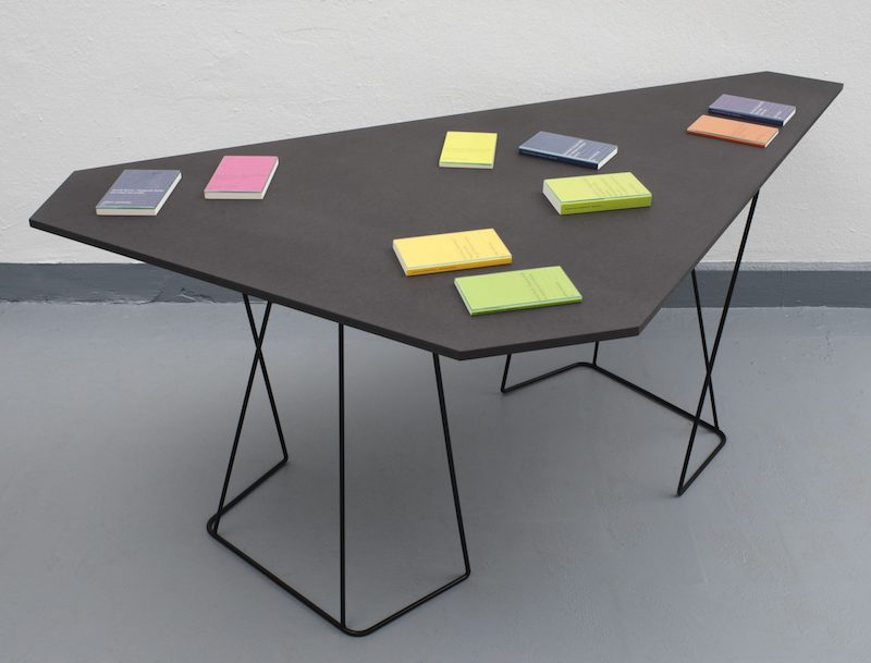 an angular black table with colorful Surhkamp books on top of it