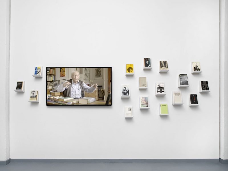the white gallery wall with small shelves the size of individual books that they hold, and a screen showing a video interview of an older man at a desk