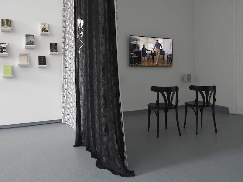the gallery room divided with a long black curtain, on one side are books mounted on small shelves on the wall and on the other is a film screening on a small tv, with two chairs in front of it