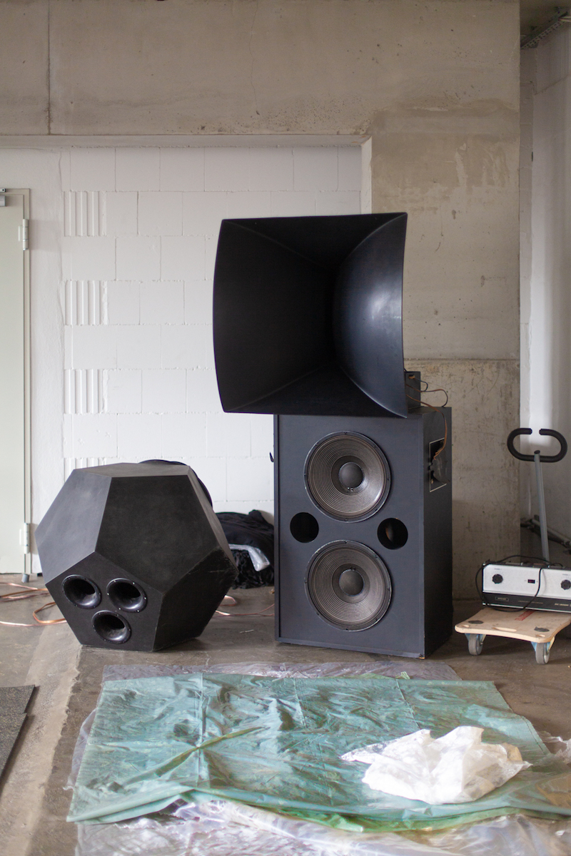 three large speakers in multiple shapes stand against the walls of the studio