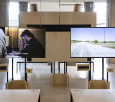 a photo of an exhibition installed in HKW with several screens and desks with chairs