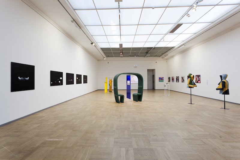 an photo of an exhibition installation with pieces mounted on the wall and a seat in the middle of the image