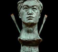 A bronze sculpture of a male head with two bronze paint brushes emerging from his neck