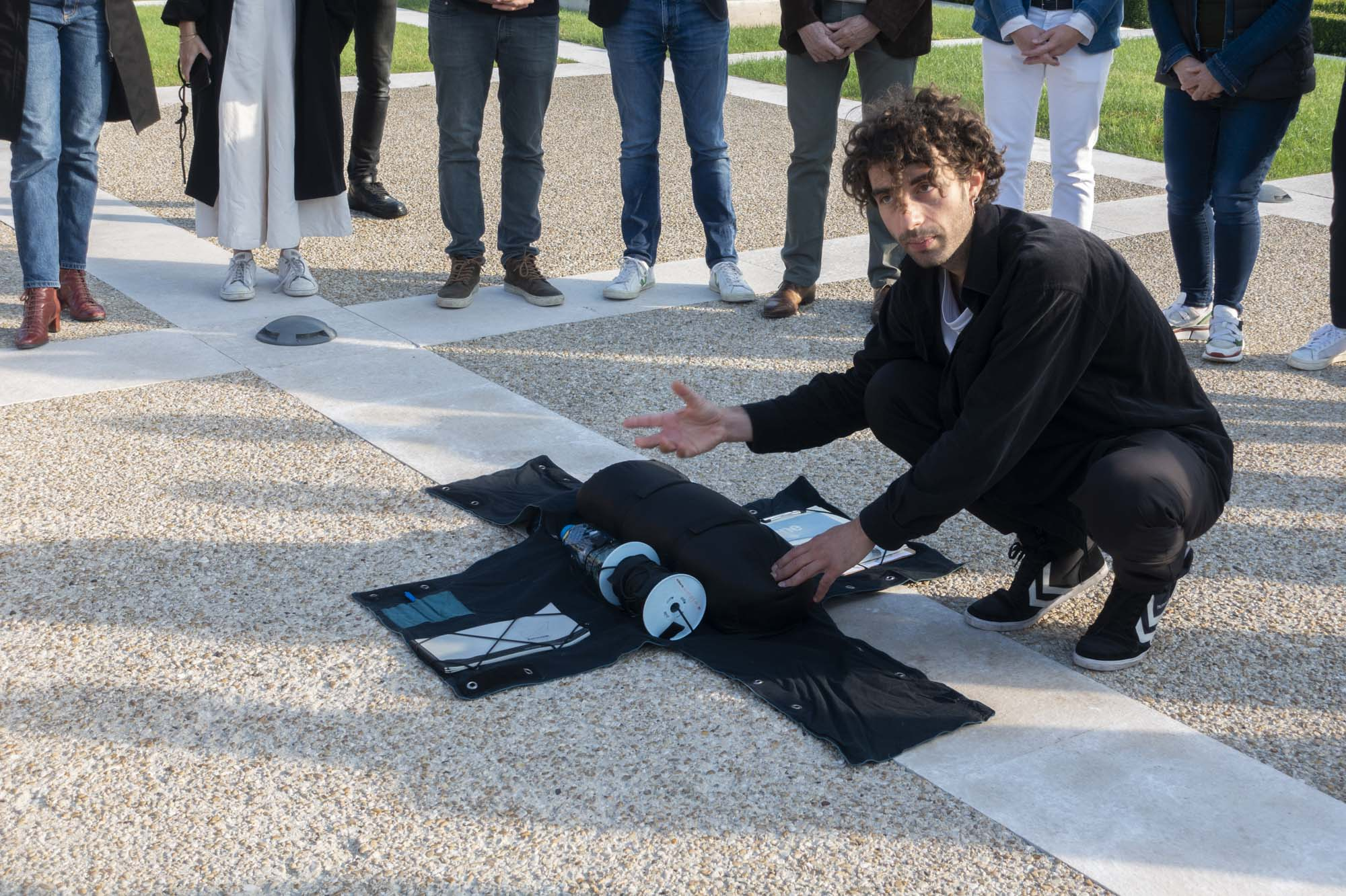 """Tomás Saraceno's assistant is presenting the """"aerocene backpack"""" outside of Maison Ruinart in Reims"""