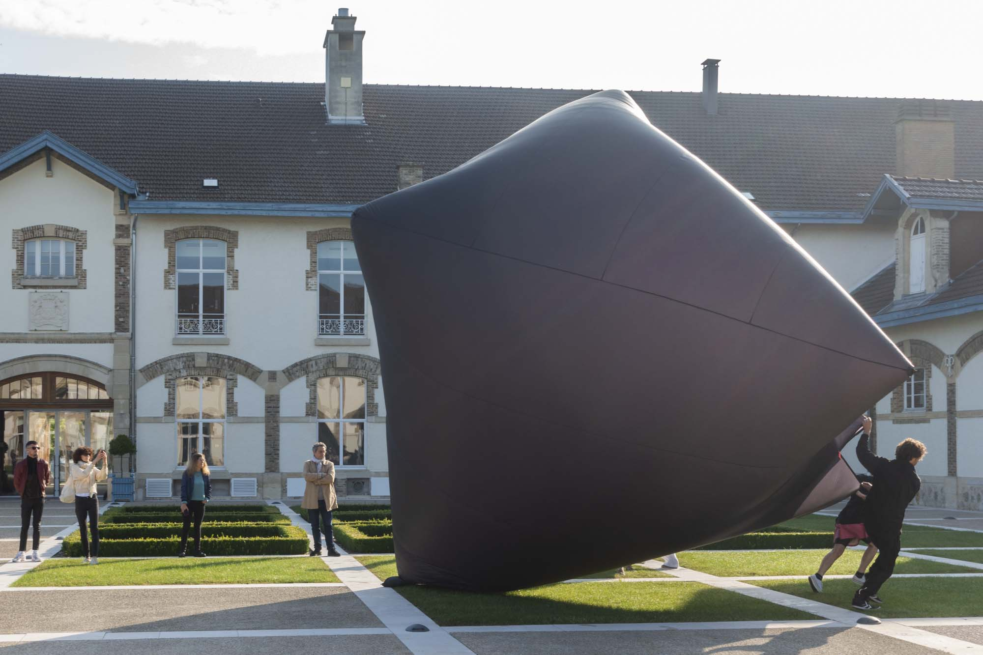 Tomás Saraceno's assistant and a journalist filling the black Aerocene sculpture with air outside of Maison Ruinart in Reims