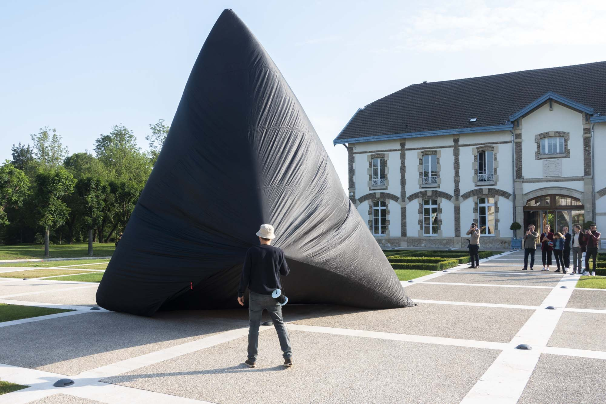 Tomás Saraceno is holding the Aerocene sculpture during his performance at Maison Ruinart in Reims