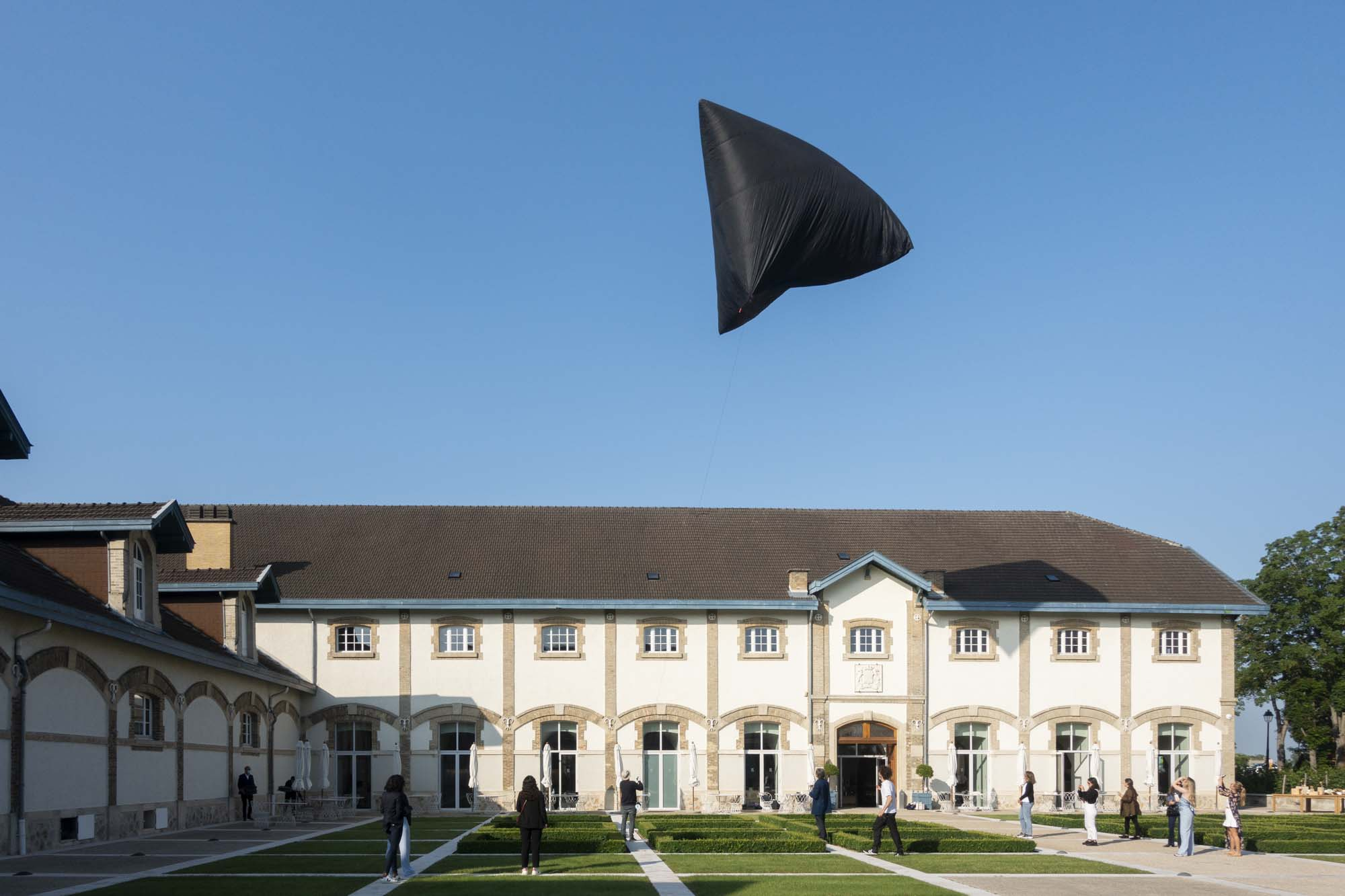 The black Aerocene Sculpture by Tomás Saraceno is floating in the sky above Maison Ruinart in Reims