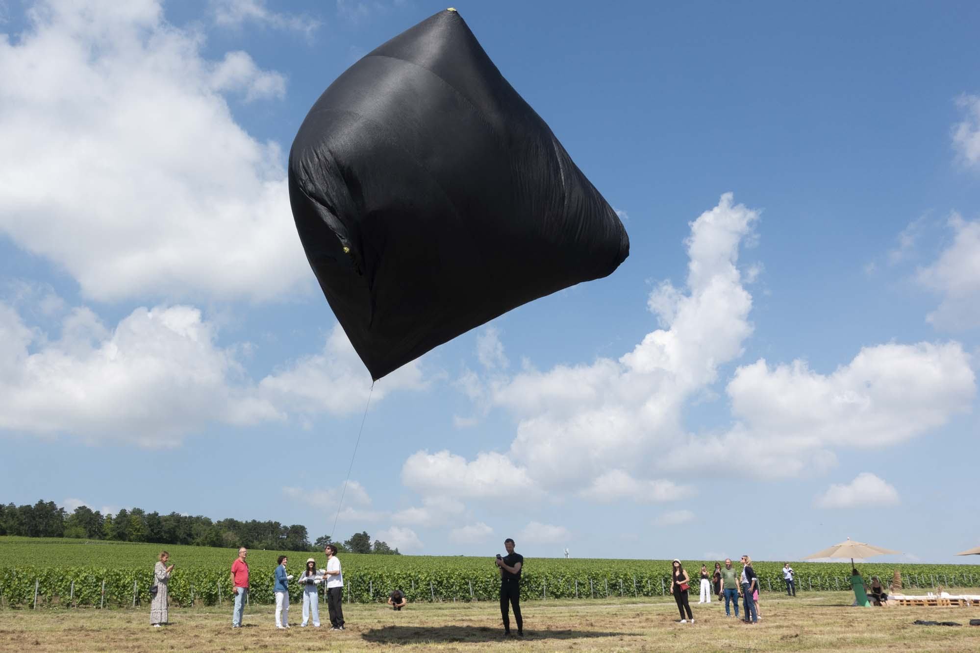 Aerocene Sculpture by Tomás Saraceno floating in the sky over the Ruinart vineyards in Champagne near Reims