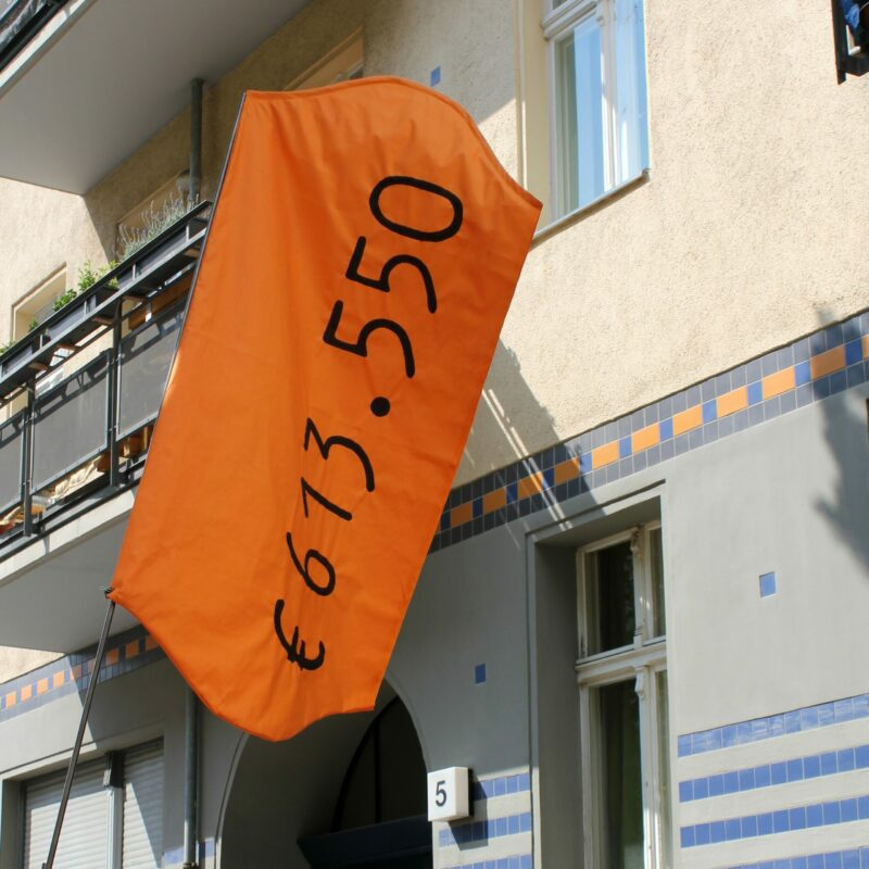 """A red flag hanging on a building, with a price tag that says """"€613.550"""""""