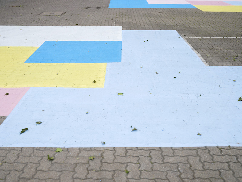 A close up of the blue, yellow, white and pink colored square shapes painted on a courtyard ground