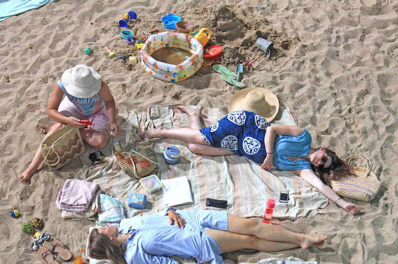 several people lie on a sandy beach, on towels, with beach toys spread around