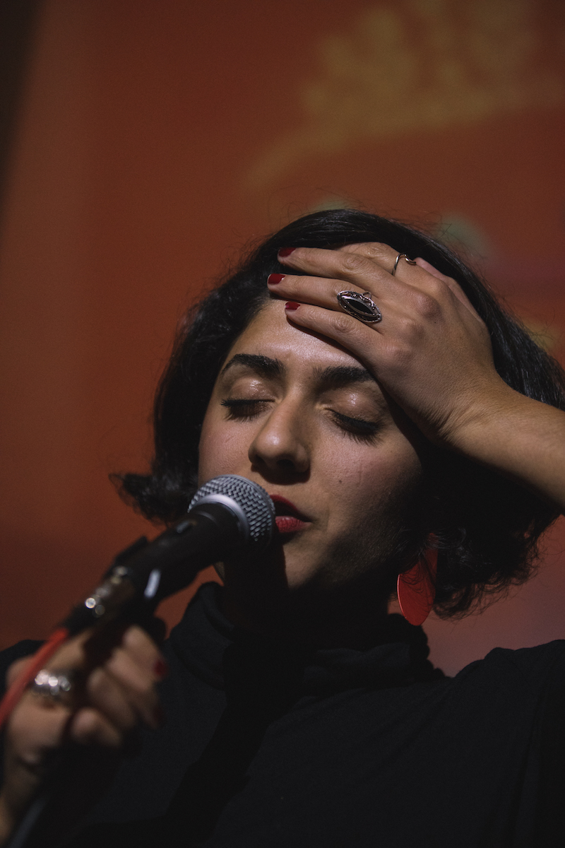 a close up of the poet speaking into a microphone while one hand is pressed against her forehead