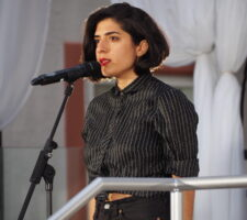 tanasgol sabbagh, a person with dark bobbed hair and red lipstick, speaks into a microphone on stage