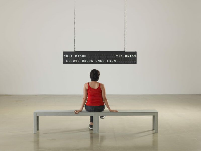 A woman is sitting in an art space on a bench looking at the artwork hanging from the ceiling