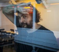 The artist Kader Attia leaning on a window