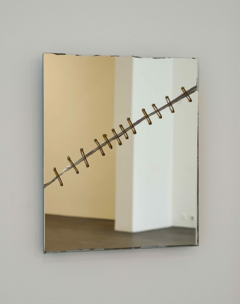 Broken and stapled mirror on a white wall